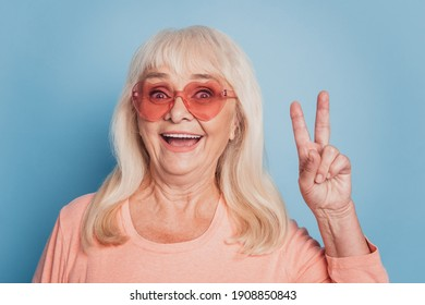 Close up portrait of mature funny lady showing v-sign