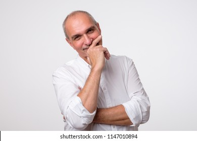 Close up portrait of mature hispanic man laughing and covering his mouth with hand over white background. Trying to hold a laugh not to offend some person. He just heard a funny joke