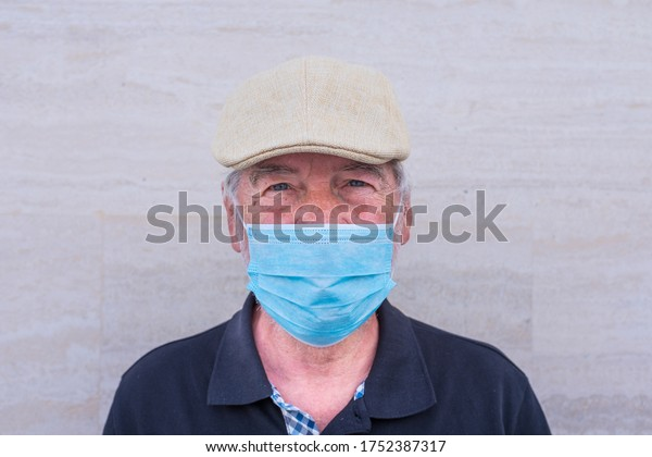 close up and portrait of mature man and senior looking at the camera seriously wearing medical and surgical mask to prevent covid-19 or any type of disease or flu
