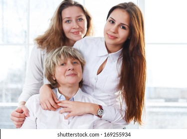Close up portrait of a mature mother and adult daughter and teen granddaughter being close and hugging at home being happy and joyful