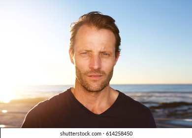 Close up portrait of middle age man standing outside staring