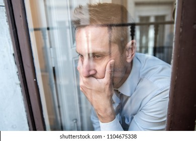 Close up portrait of middle aged man sad and depressed looking through the window refection, thinking about his life suffering depression in mental health concept