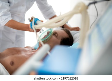 Close up portrait of middle aged man with oxygen mask lying in bed. Doctor hands using respiratory equipment to restore lungs function of gentleman
