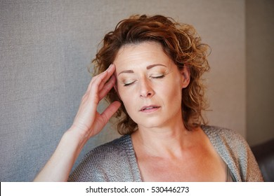 Close up portrait of middle aged woman with hand to head in pain