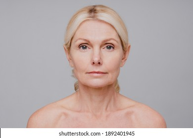 Close up portrait of middle-aged beautiful woman showing her beauty isolated over grey background