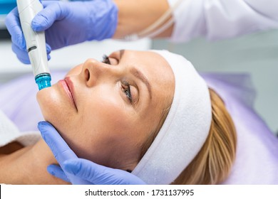 Close up portrait of a middle-aged female patient undergoing a facial hydro vacuum microdermabrasion peeling treatment