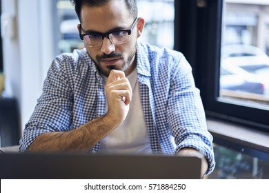 Close up portrait of mindful male blogger in eyewear watching streaming video of workshop to write feedback article on personal web page concentrated on work using laptop and wireless internet