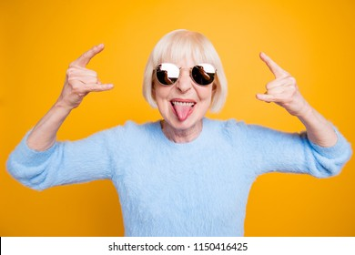 Close up portrait of  modern granny hold hands up and showing sign rock and roll isolated on yellow background