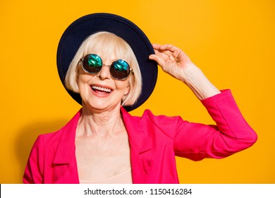 Close up portrait of modern old lady hold han in the hands and looking at camera isolated on vivid yellow background