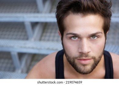 Close up portrait of a modern young man with beard staring