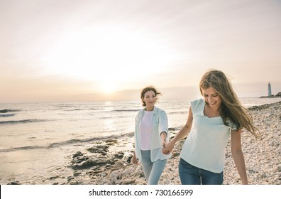 Close up portrait of mom and her teenage daughter hugging and smiling together over sunset sea view. Beautiful woman relaxing with her child.