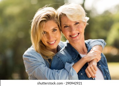 close up portrait of mother and daughter hugging