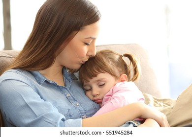 Close up portrait of a mother kissing to her asleep baby daughter sitting on a sofa in the living room at home with a warm light