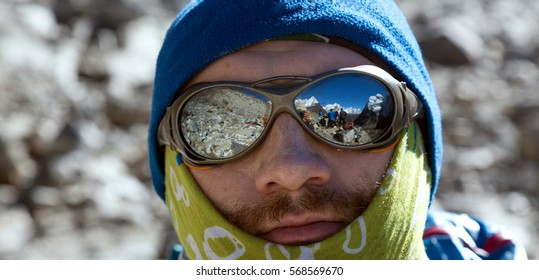 Close Up Portrait of Mountain Climber in warm Cap Head Band and protective Sunglasses