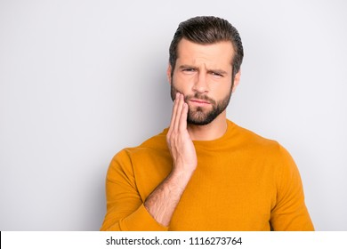 Close up portrait of nervous unhappy troubled handsome bearded man touching his cheek he has toothache isolated on gray background copy-space