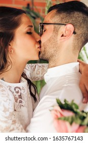 Close up portrait of newlywed couple with close eyes caressing and kissing on their wedding day. Love concept.