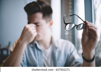 Close up portrait of a nice stulish man holding glasses in his left hand. Tired guy from reading or working rubbing his nose and eyes