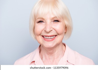 Close up portrait of old adult caucasian blonde glad cheerful lady smiling, over grey background, isolated