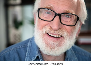 Close up portrait of old bearded smiling man looking at camera with excitement. He is open-eyed and amazed