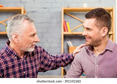 Close up portrait of old father and his happy son laughing