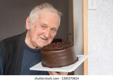 Close up portrait of old happy business man and holding chocolate Cake