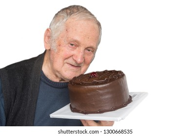 Close up portrait of old happy business man holds chocolate cake on a white isolation background.
