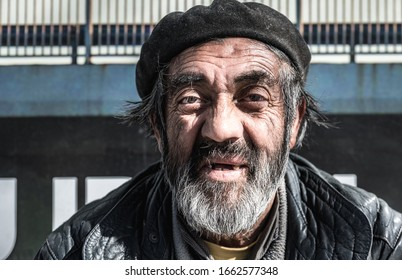 Close up portrait of old homeless alcoholic man face with white beard and hair wandering on the street depressed sick and lonely, social issues homelessness documentary concept