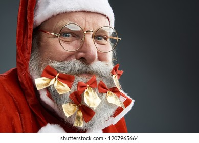 Close up portrait of old man in Santa costume looking at camera with sly smile. He is wearing glasses