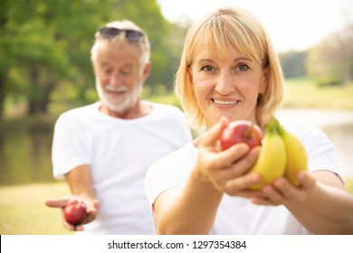 Close up portrait of older woman holding fruit in hand. Healthy diet