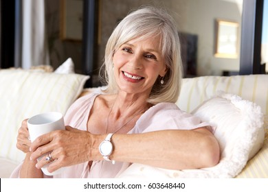 Close up portrait of older woman sitting on couch with coffee