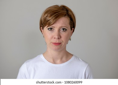 close up portrait os a beautiful young red haired caucasian woman with a serious face. Beautiful eyes looking straight at the camera. Human facial expressions and emotions. Gray background