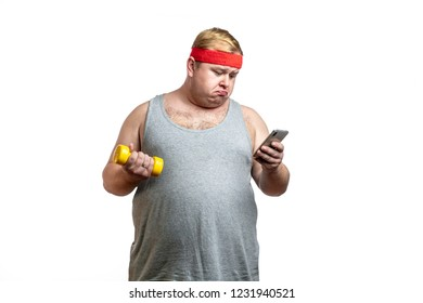close up portrait of overweight obese man holding in one hand little dumbbell and reading smth at smartphone at the same time, being displeased with poor fitness results in sport trainings
