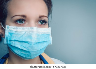 Close up portrait of pensive female doctor or nurse wearing protective mask