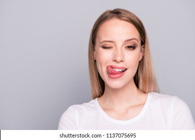 Close up portrait of playful and sweet girl showing tongue giving wink isolated gray background with copy space for text
