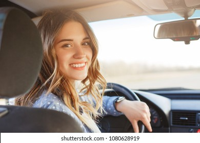 Close up portrait of pleasant looking female with glad positive expression, being satisfied with unforgettable journey by car, sits on driver`s seat, enjoys music. People, driving, transport concept - Shutterstock ID 1080628919