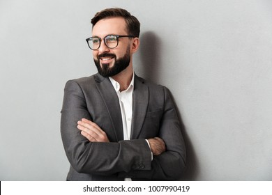Close up portrait of pleased unshaved man in eyeglasses looking on camera with sincere smile standing with arms folded isolated over gray background