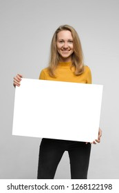 Close up portrait of positive laughing woman wearing black jeans and yellow t-shirt with blondie hair, toothy smile is holding white big mockup poster isolated on white background