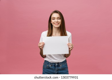 Close up portrait of positive laughing woman smiling and holding white big mockup poster isolated on pink background