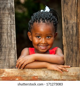 Close up portrait of pretty african youngster leaning on wooden fence outdoors.