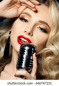 Close up portrait of pretty blond female singer holding retro styled microphone. Beautiful makeup with red lips. Concert, karaoke, celebrity, musical show or night club concept.