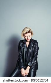Close up portrait of a pretty blonde woman, wearing black biker jacket, sadly looking down, against plain studio background