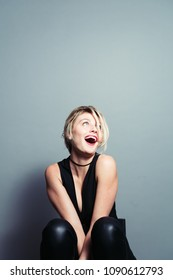 Close up portrait of a pretty blonde woman, laughing and looking to the side, against plain studio background
