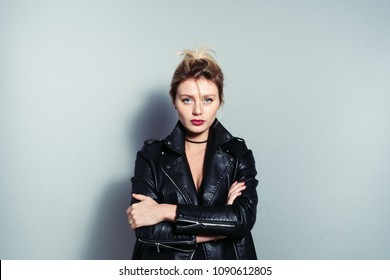 Close up portrait of a pretty blonde woman, wearing black biker jacket, looking at camera, against plain studio background