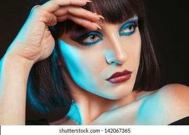 Close up portrait of pretty brunette in studio on dark background