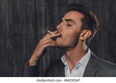 Close up portrait of pretty businessman smoking a sigarette