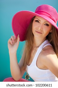 Close portrait of pretty cheerful woman wearing white dress and straw pink hat in sunny warm weather day near the sea