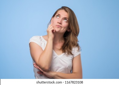 Close up portrait of pretty confident thoughtful girl looking like conspirator. She ponders plans for tomorrow, compiles a list of tasks or shedule. What is better to choose concept