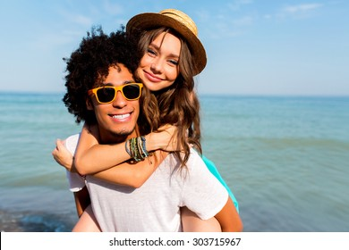 Close up portrait of pretty couple in love  having fun on beach holidays together. Stylish hipster lovers posing on  amazing  beach blue ocean background.