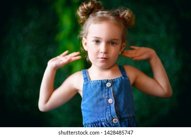 A close up portrait of a pretty girl in a denim sundress posing over the green background. Kids, fashion, beauty.