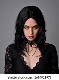 Close up portrait of a pretty, goth girl with dark hair  posing in front  a studio background.